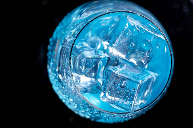 Blue cocktail with ice cubes. Top view