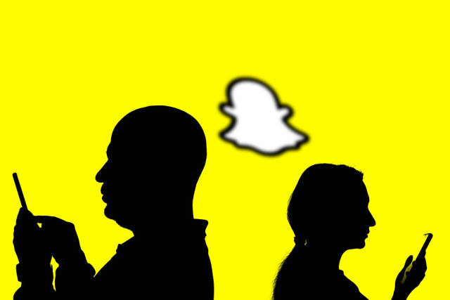 People silhouettes over popular Snapchat logo