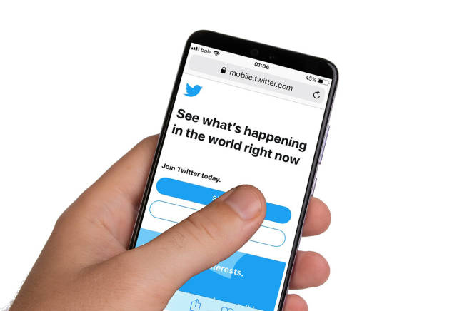 Male hands holding smartphone with an open Twitter application