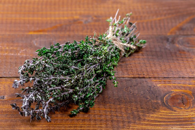 Fresh bouquet of thyme spices on brown boards