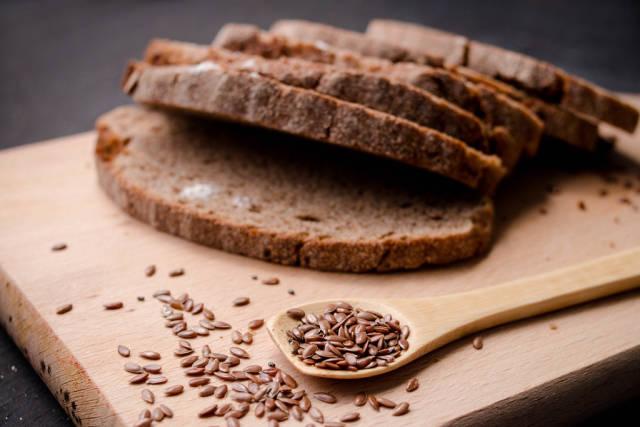 Slices of  dark  fresh bread with  seeds on dark wooden background