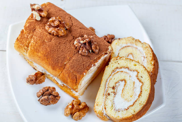 Top view homemade biscuit roll with cream and walnuts