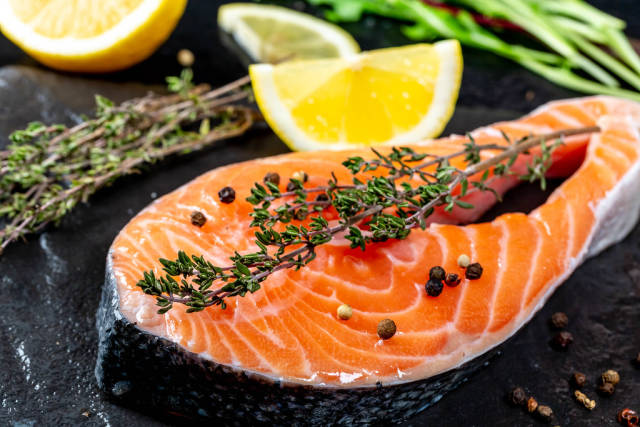 Close-up of raw salmon with fresh thyme and lemon slices