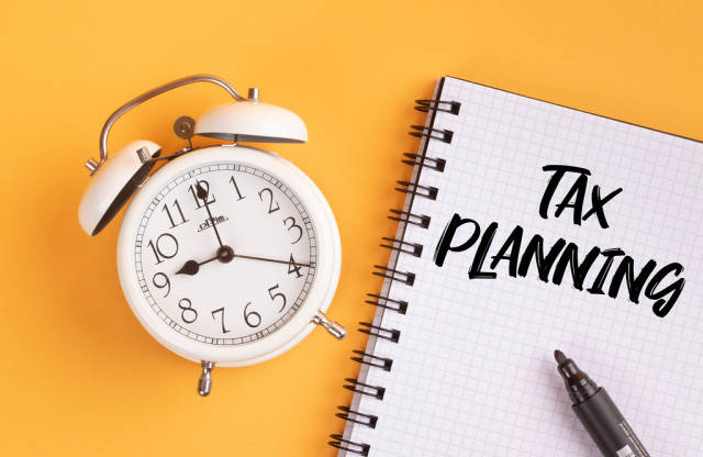 Alarm clock with handwritten text Tax Planning on yellow background