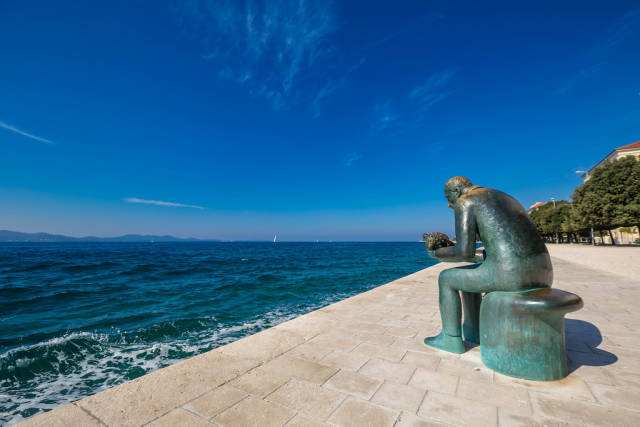 Statue of man with a seashell on promenade