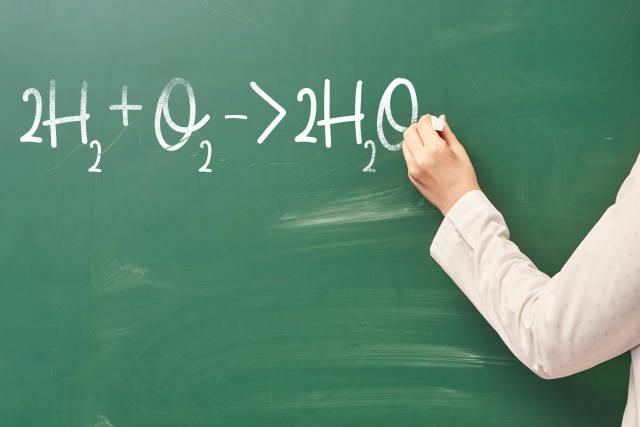A person writes on a chalkboard chemistry formula