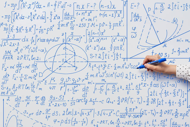 Teachers hand writing complicated mathematical formulas on the whiteboard