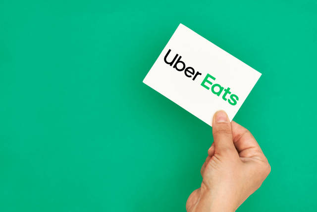 Hand holding a logo of famous takeaway delivery service Uber Eats on green background