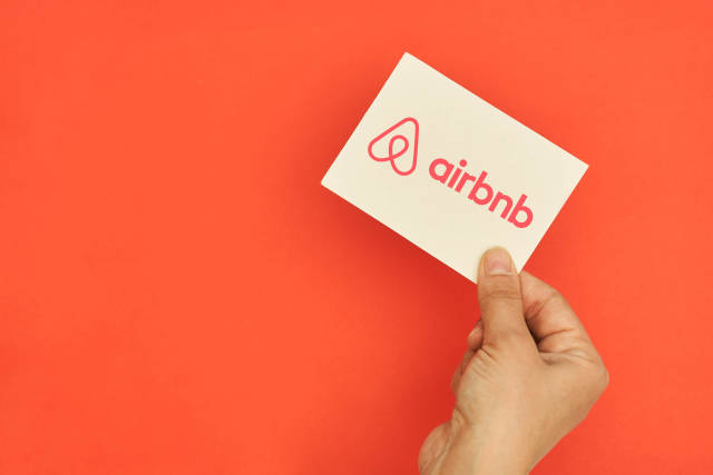 Hand holds Airbnb logotype card over red background