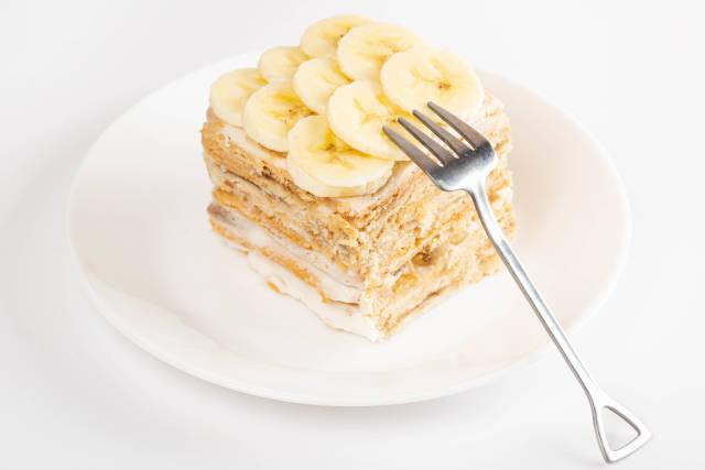 Piece of homemade cake with cream and fresh bananas