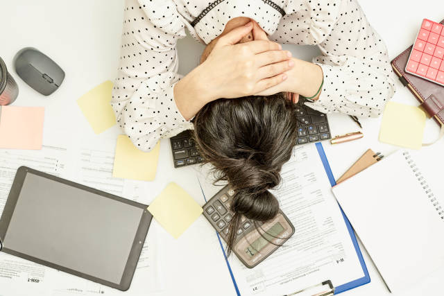 Overhead view of overloaded office worker sleeping at workplace