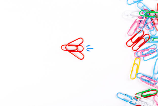 Many multicolored paper clips and plane made of paper clips on white