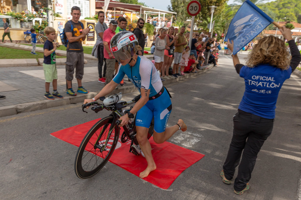 A barefoot woman jumps on her bike at a triathlon in Paguera