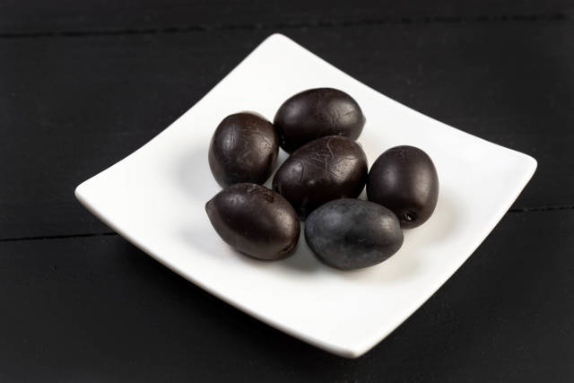 Cleaned Black Olives served on the square plate