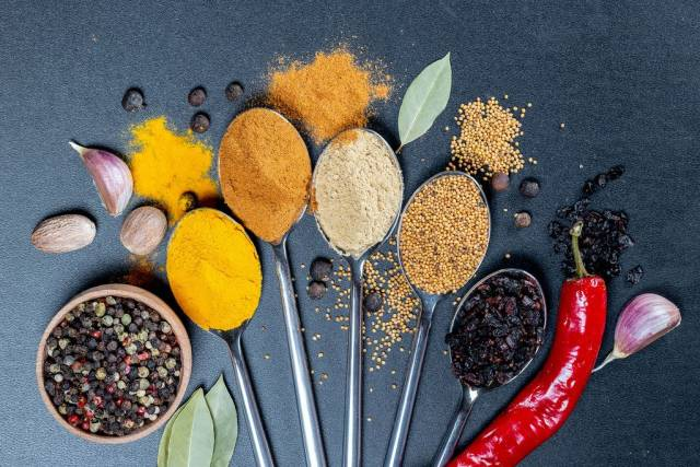 Top view on spices on spoons - curcuma, curry, garlic, mustardseeds and barberries with nutmeg in front on black background