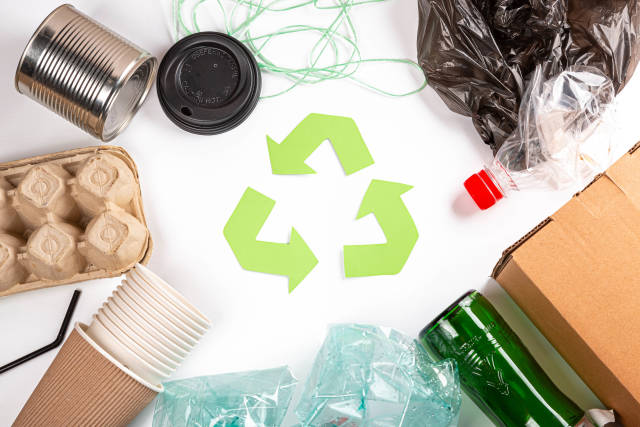 A selection of garbage for recycling, plastic, paper and glass with green waste recycling symbol, top view