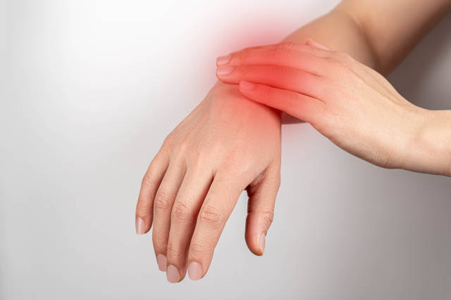 Pain in the wrist, female hands close-up