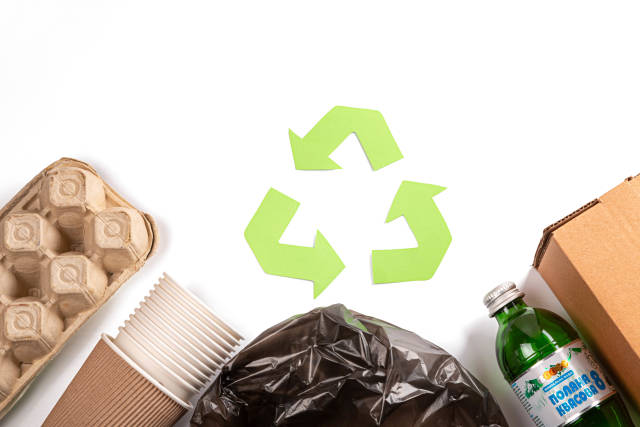 Recycle concept, green arrows icon among waste on white background, top view