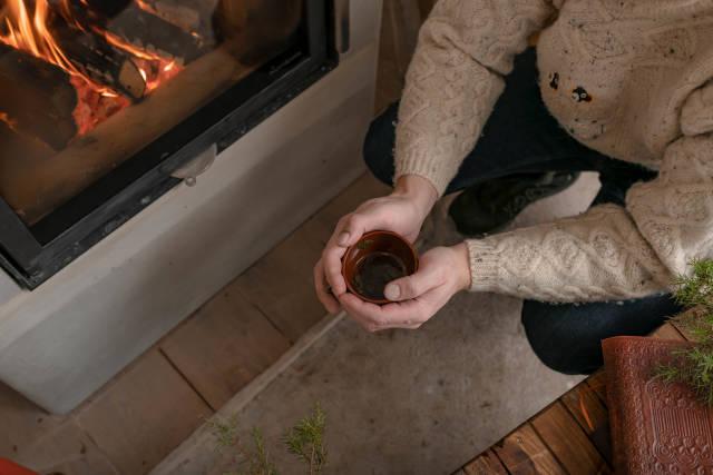 Holding Hot Tea Near FirePlace