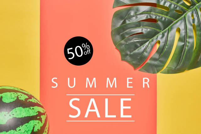 Summer sale with palm leaves and ball on a bright color background