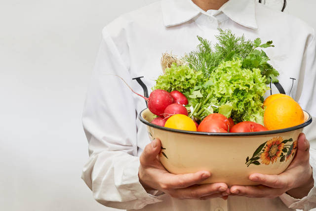 A woman with a bowl full of fresh vegetables