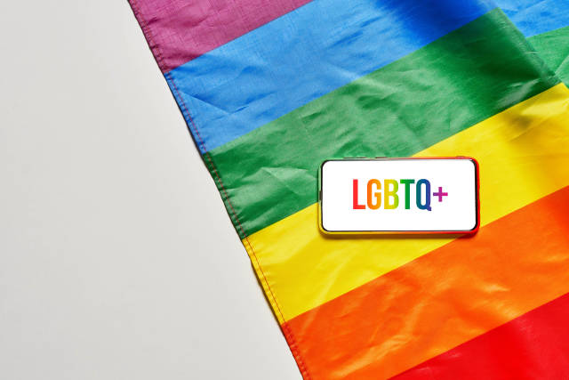 Smartphone with LGBTQ+ text on screen and rainbow flag