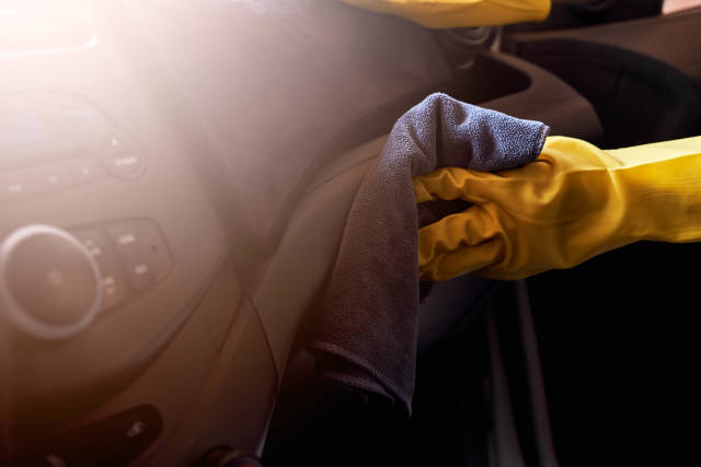 Car cleaning service - hand in rubber gloves cleaning car interior panel with a cloth