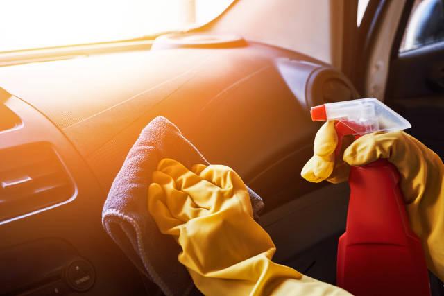 Car washing service worker cleaning car dashboard
