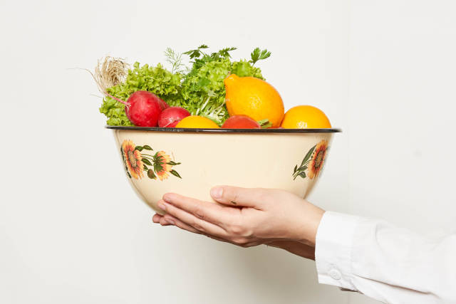 Hand holding a big bowl full with fresh fruits and vegetables