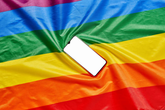 Colorful rainbow flag and mobile phone with blank screen