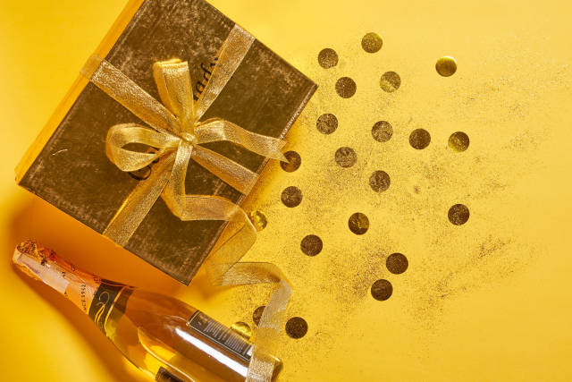 Birthday gift, festive confetti and champagne bottle on yellow background