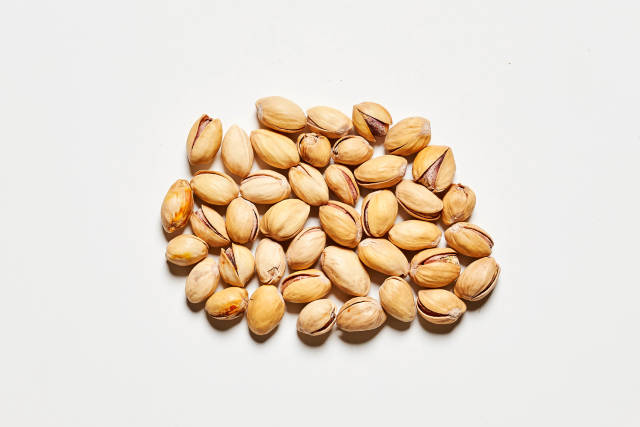 Pile of pistachios in the peel on a white background