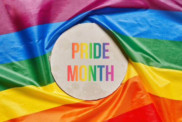 Note Pride month over a rainbow lgtbt flag