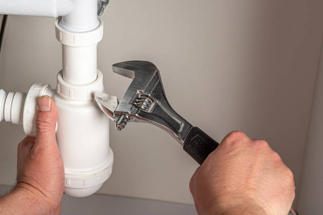 Plumber with adjustable wrench repairing pipes