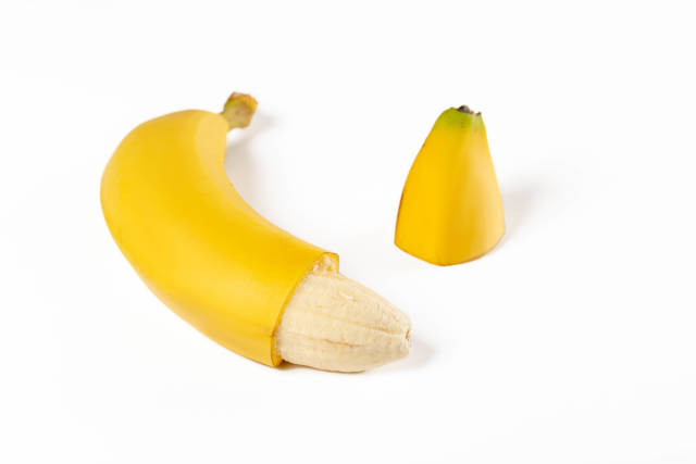 Ripe banana with the cut off part of a peel