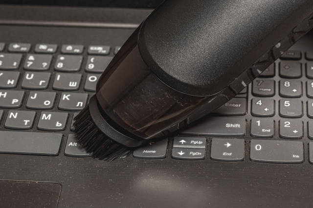 Close-up, a portable vacuum cleaner with a brush attachment collects dust on the keyboard