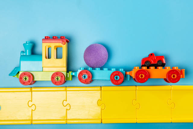 Childrens plastic constructor steam locomotive with toys and road on blue background