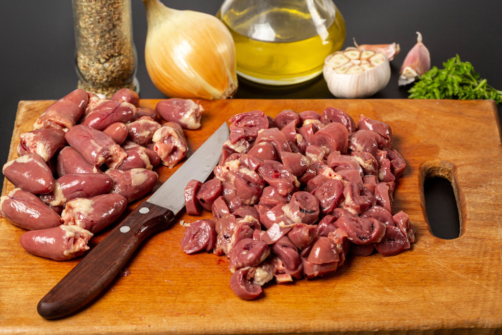 Sliced and whole raw chicken hearts with knife on cutting board