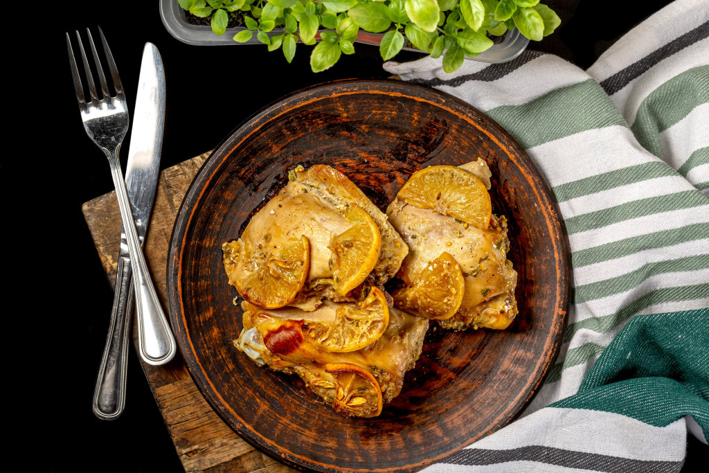Baked chicken thighs with spices and lemon, top view