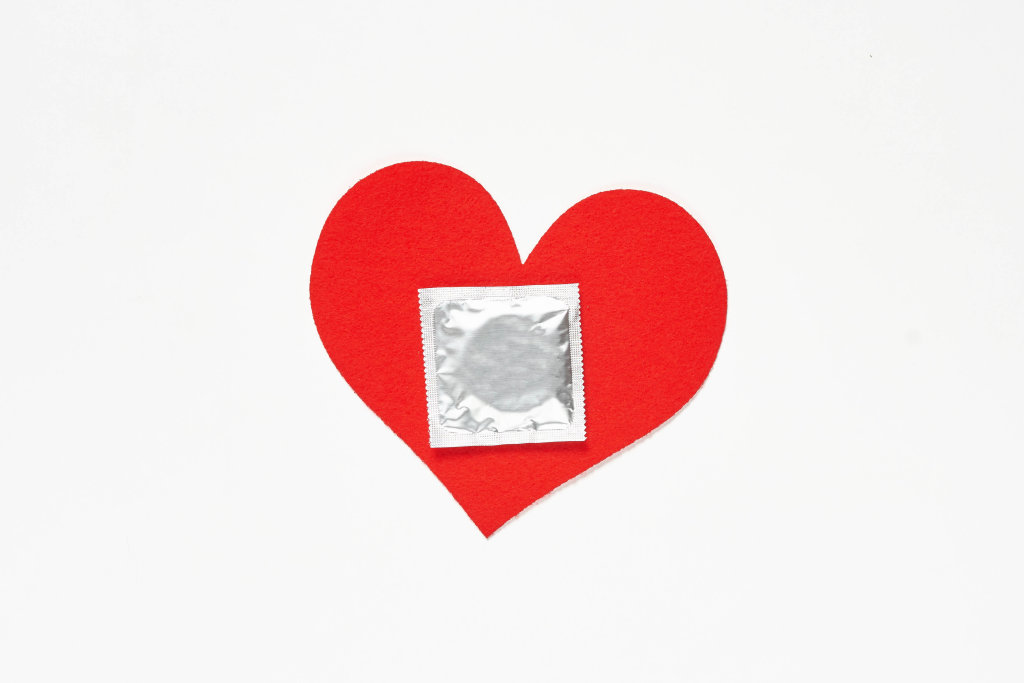 Heart shape paper cut and condom on white background