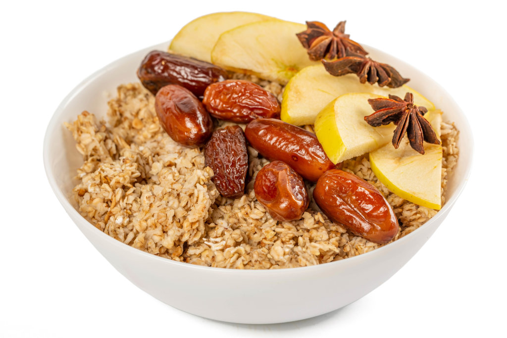 Healthy breakfast - oatmeal with apple slices, dates and star anise