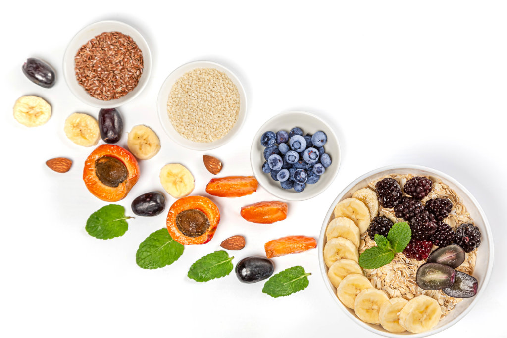 Top view of oatmeal, fruits, seeds and mint leaves on white