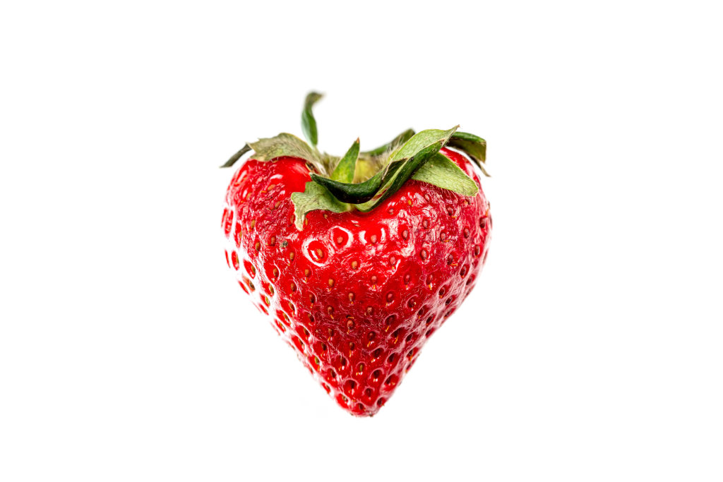 Heart shaped strawberry on white