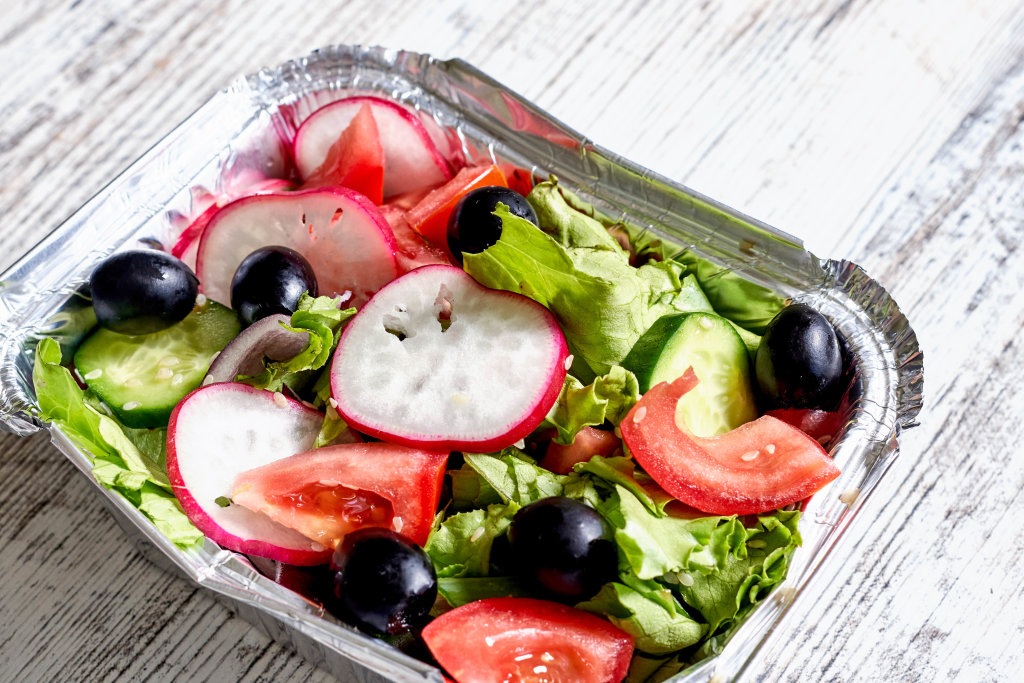 Carry out container with dieting green salad with onion and black olives
