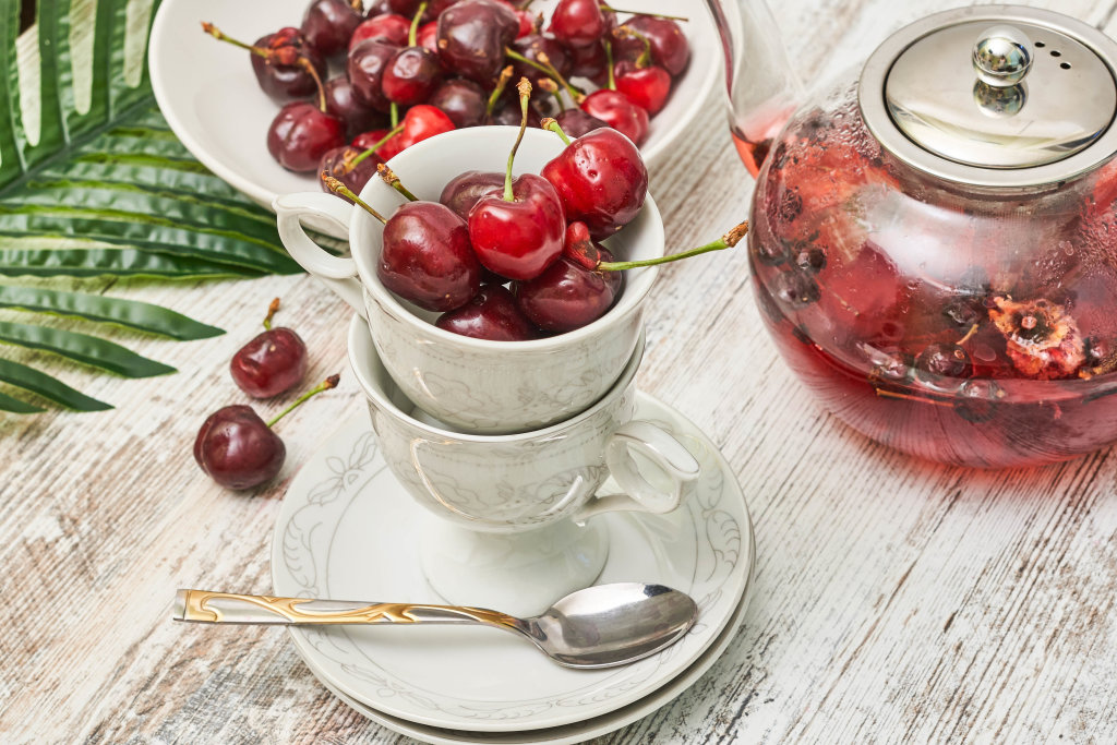 Cups full of sweet cherry fruits and teapot with fruit tea
