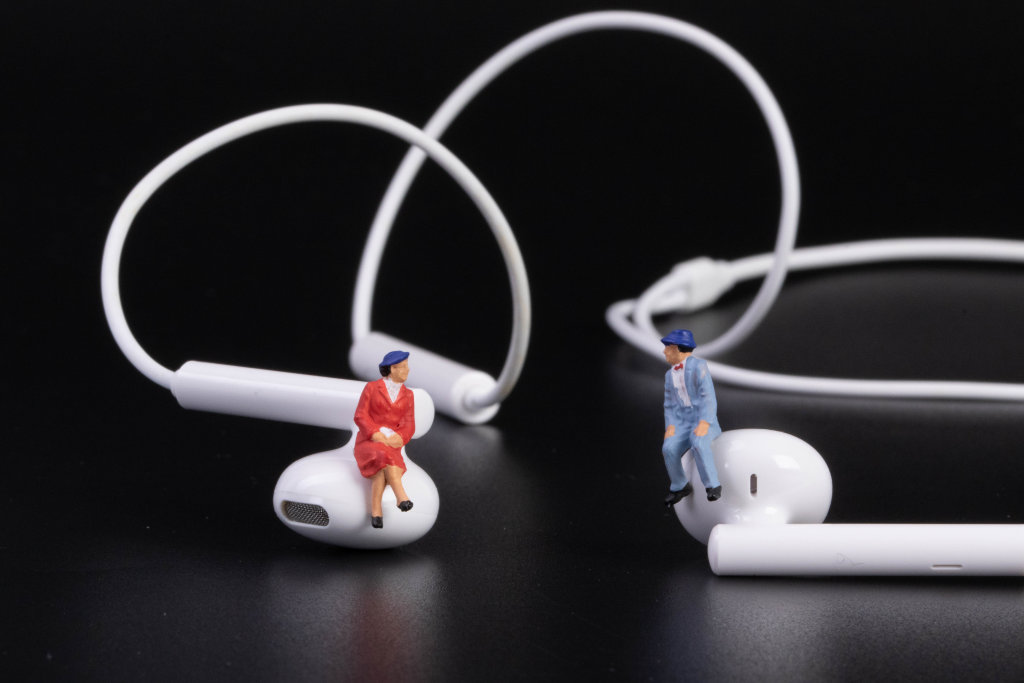 Older couple sitting on earbuds