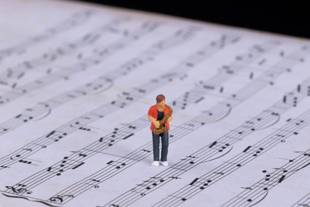 Miniature saxofonist standing on music notes