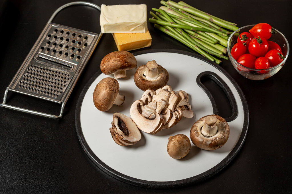 Fresh vegetables and mushrooms on a dark background with cheese and grater