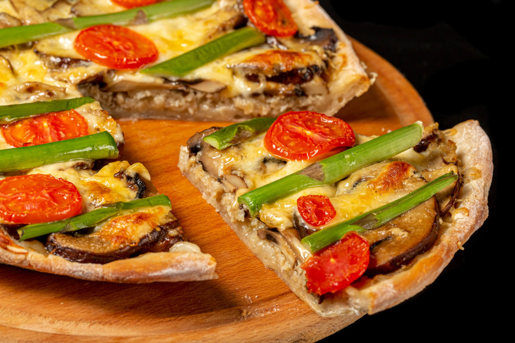 Close-up, hot slice of pie with mushrooms, meat, cheese, tomatoes and asparagus