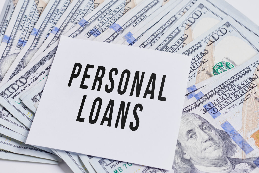 A pile of us dollars and a piece of paper with Personal loans text